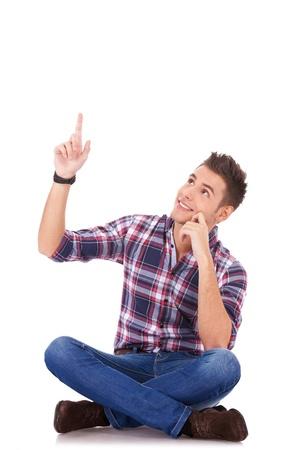 hombre sentado: sentado joven informal apuntando a algo, por encima de su cabeza, sobre fondo blanco