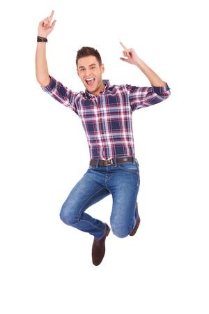 jumping: Hombre guapo saltando de la alegría de la victoria sobre fondo blanco