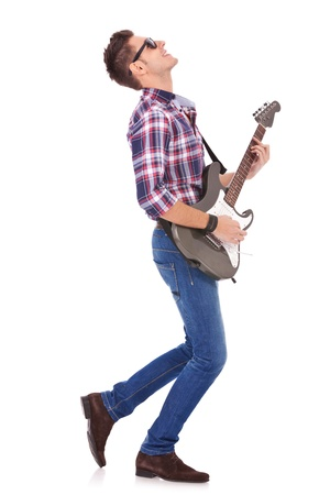 side view of a passionate guitarist playing his electric guitar on white background  Stock Photo