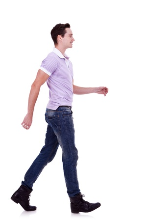 man side: side view of a fashion man walking forward over white . young casual man walking from left to the right of the camera   Stock Photo