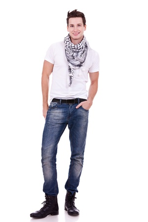 teenagers standing: young casual man wearing boots, jeans and scarf looking at the camera on white background