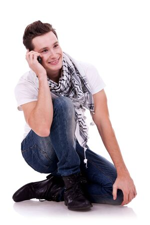 crossed legs: seated young man talking on the phone and looking pensive and sliling