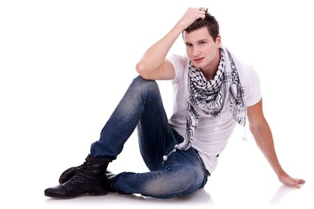 young casual happy man seated on studio, on white background photo
