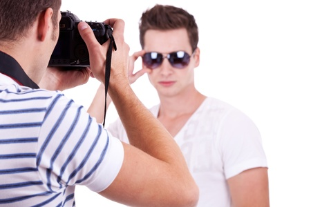 young male fashion model posing for a professional photographer on white background. young man wearing sunglasses being photographed by a young artist   photo