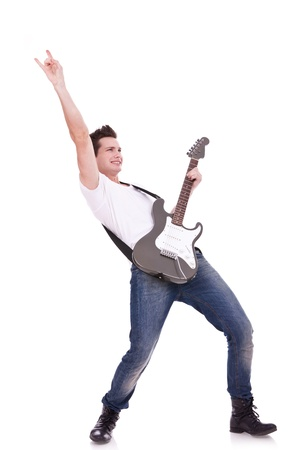 Rock star with a guitar making a rock and roll gesture isolated over white background  photo