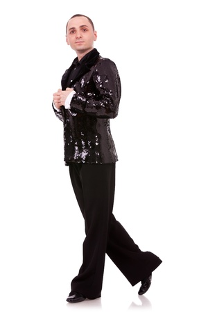 latino male dancer posing. isolated on white . full body of a man salsa dancer looking at the camera , wearing a flashy shinny black suit photo