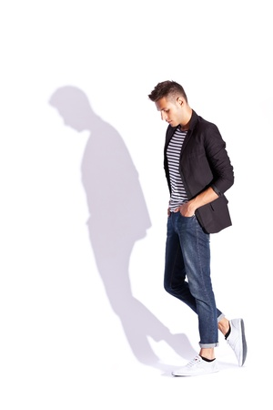 man looking down: side view of a fashion young man with hands in pockets, looking down, on white background with hard shadow