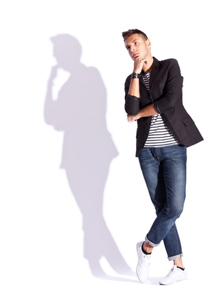 full body shot: cool looking shadow of a young casual man in a fashion pensive pose, on white background