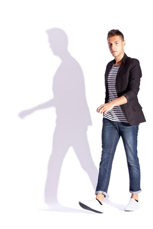 full body shot: side view of a young casual fashion man  walking on a white background with hard shadow