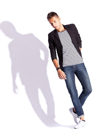 young fashion man in shirt, coat and jeans standing on white background with hard shadow Stock Photo - 13890860