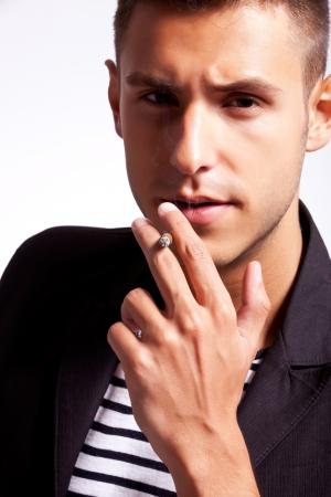hombre fumando puro: Primer plano de un joven que fuma un cigarrillo Foto de archivo