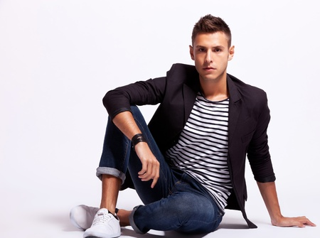 Portrait of a casual young fashion man sitting relaxed on gray background Stock Photo - 13890922