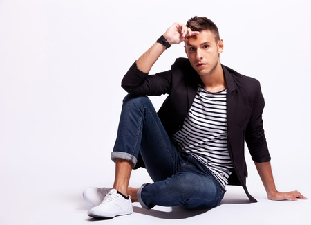 fashion male model looking serious while sitting on a gray background