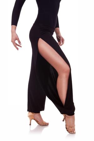 baile latino: las piernas de una bailarina de salsa de la mujer joven en el fondo blanco