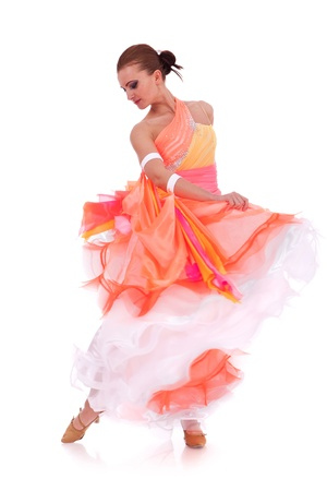 sensual waltz dancer pulling up her long orange dress on white background photo