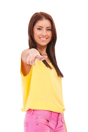 Young female pointing at you - Portrait of an attractive young woman pointing her finger. Isolated on white background Stock Photo - 13890822