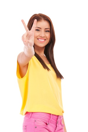 portrait of young smiling woman with victory gesture on white background photo