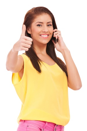 casual woman on the phone with her thumbs up , isolated on white background  photo