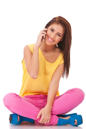 hablando por celular: mujer sonriente informal está sentado y hablando por teléfono móvil aislado en blanco