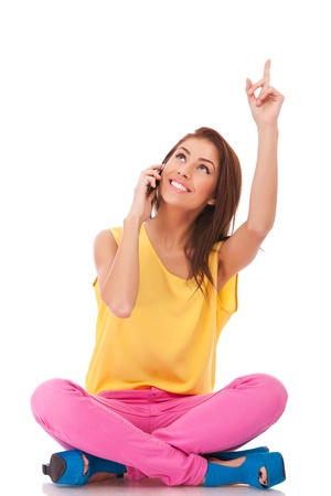 woman pointing up: young seated casual woman talking on the phone, pointing and looking up to something
