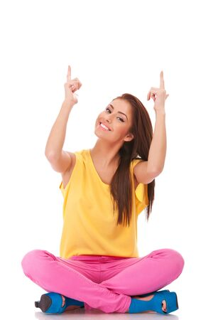 woman pointing up: seated young casual woman pointing up over her head with both her hands on white background