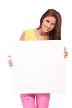Attractive casual young  woman holding a  blank board on white background photo