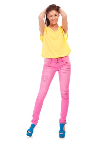 full body picture of a young pretty woman with hands in her hair and wearing casual colorful clothes  against white background photo