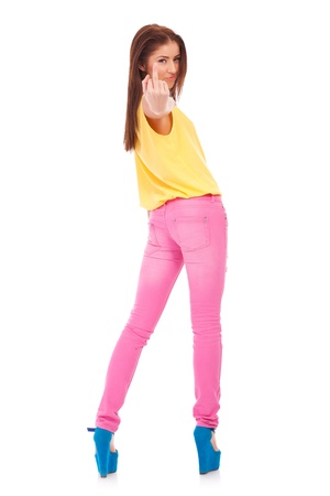 back of a young casual woman giving the middle finger on white background photo