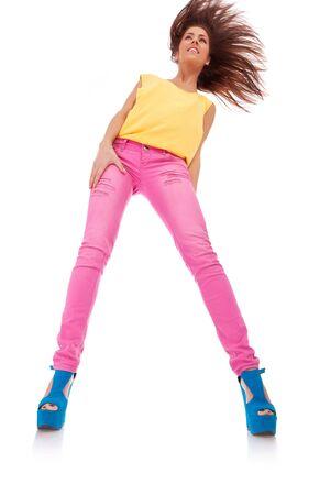 bellow: imagen de gran angular desde abajo de una joven informal con el pelo ondeando bonita, sobre fondo blanco