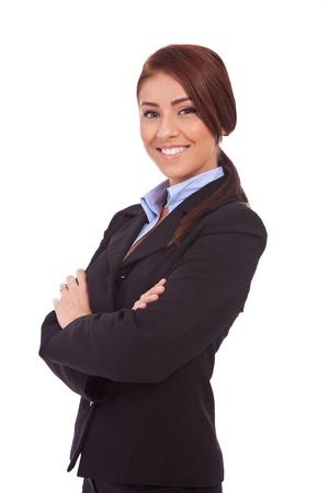 mani incrociate: Ritratto di bella donna d'affari giovane sorridente, in piedi con le braccia incrociate su sfondo bianco Archivio Fotografico