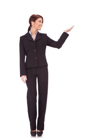 cuerpo completo: foto de cuerpo entero de una mujer de negocios que presenta algo imaginario sobre fondo blanco