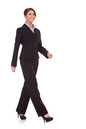 caminando: foto de cuerpo entero de una mujer caminando de negocios aislados sobre un fondo blanco Foto de archivo