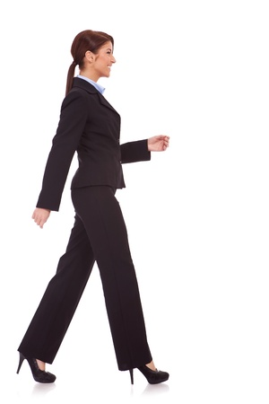 side view of a young business woman walking. She is smiling and looking away from the camera isolated over white background