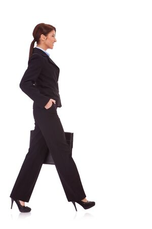 Portrait of successful business woman walking with a briefcase - White background  photo