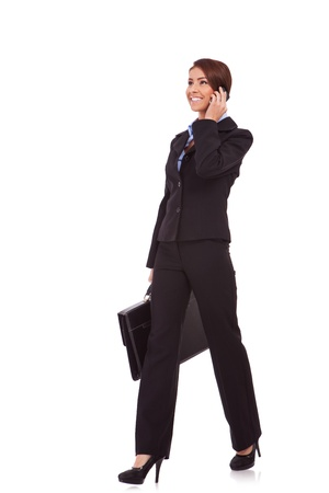side view of a young business woman talking on the phone and holding a brief case while walking on white background photo