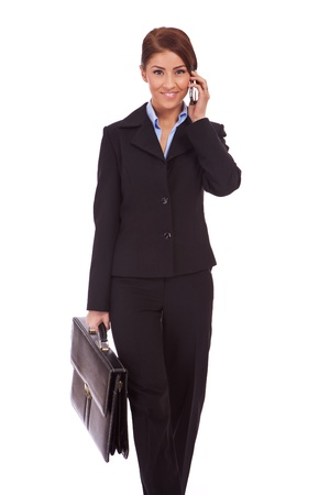young business woman with briefcase talk on the phone and walking towards the camera photo
