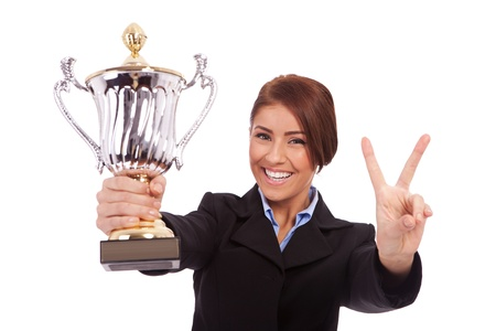 business woman holding a trophy and making victory gesture on white background photo