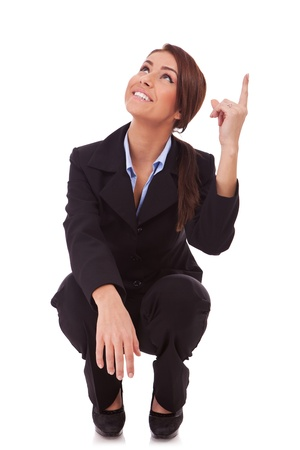 Successful business woman standing down and pointing up,  on white background  photo