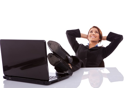 Thinking office worker day dreaming looking up smiling happy. Young business woman in suit sitting at office desk with laptop. Stock Photo - 13986550