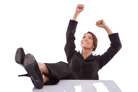 winning business woman: relaxed and winning business woman sitting with her legs on desk and hands in the air