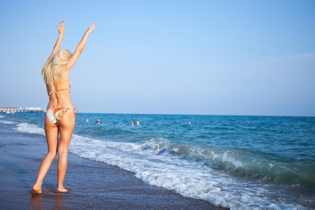 sexy woman standing on the beach with her hands inthe air photo
