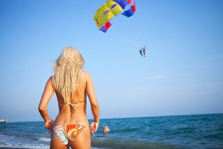 paragliding: sexy woman standing on the beach looking forward to a paragliding adventure on her vacation