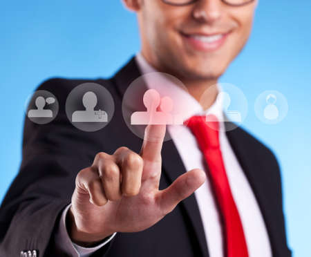Business man pressing round social buttons on a virtual background photo