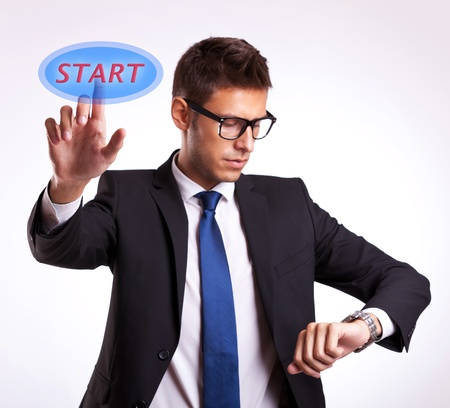 young man checking his wrist watch and pushing start button on a virtual creen photo