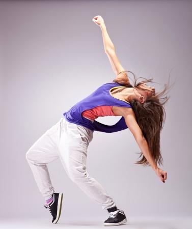 Bailarín de la mujer hermosa en traje del salto de la cadera pulso una actitud Foto de archivo