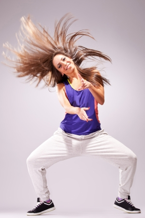hip hop dance: headbanging woman dancer standing on a leg in a full of energy dance move and screaming