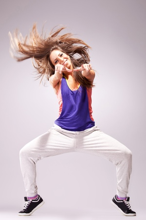 young stylish girl dancing modern ballet dance , with a headbanging move and pointing to you photo