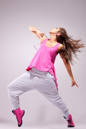 breakdance: Young woman dancer posing in a full of energy dance move. On gray background Stock Photo