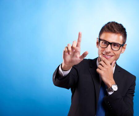 hombre empujando: Joven hombre de negocios empujando imaginarios botones digitales. Cool Man con gafas. Foto de archivo