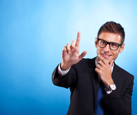 Young business man pushing imaginary digital buttons. Cool man with glasses.  photo